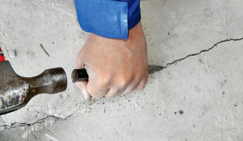 clean a crack in the floor with a chisel